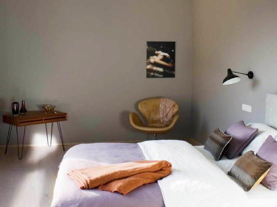 Bett mit lila Tagesdecke