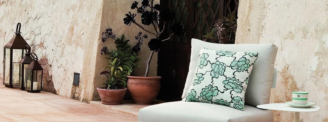 Stuhl mit Blumenkissen und Beistelltisch