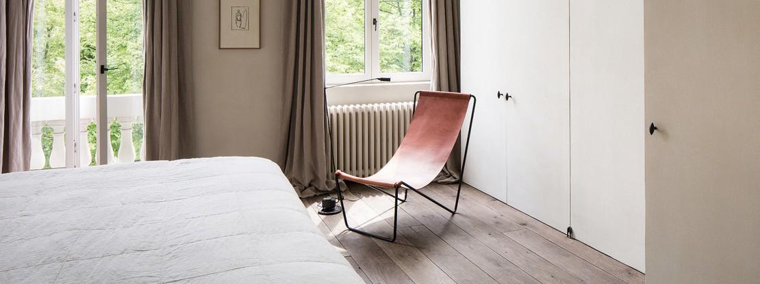 Schlafzimmer mit Einbauschränken und Stuhl