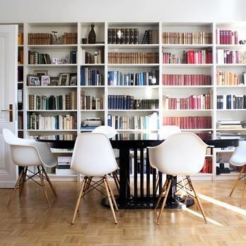 Esszimmer mit Bücherwand im Hintergrund