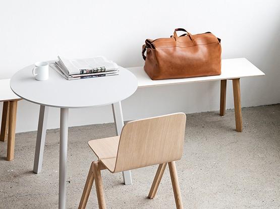 Tisch mit Holzstuhl und Ledertasche