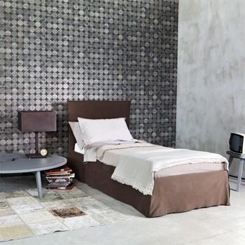 Einzelbett mit großem Beistelltisch und Tischlampe